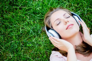 Peaceful woman listening to music with headphones outdoors